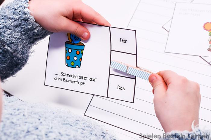 Grundschüler können Begleiter üben mit diesen niedlichen Artikelklammerkarten zur Gartenarbeit. Mit Anleitungskarten und passendem Blatt zum Schreiben der Sätze.